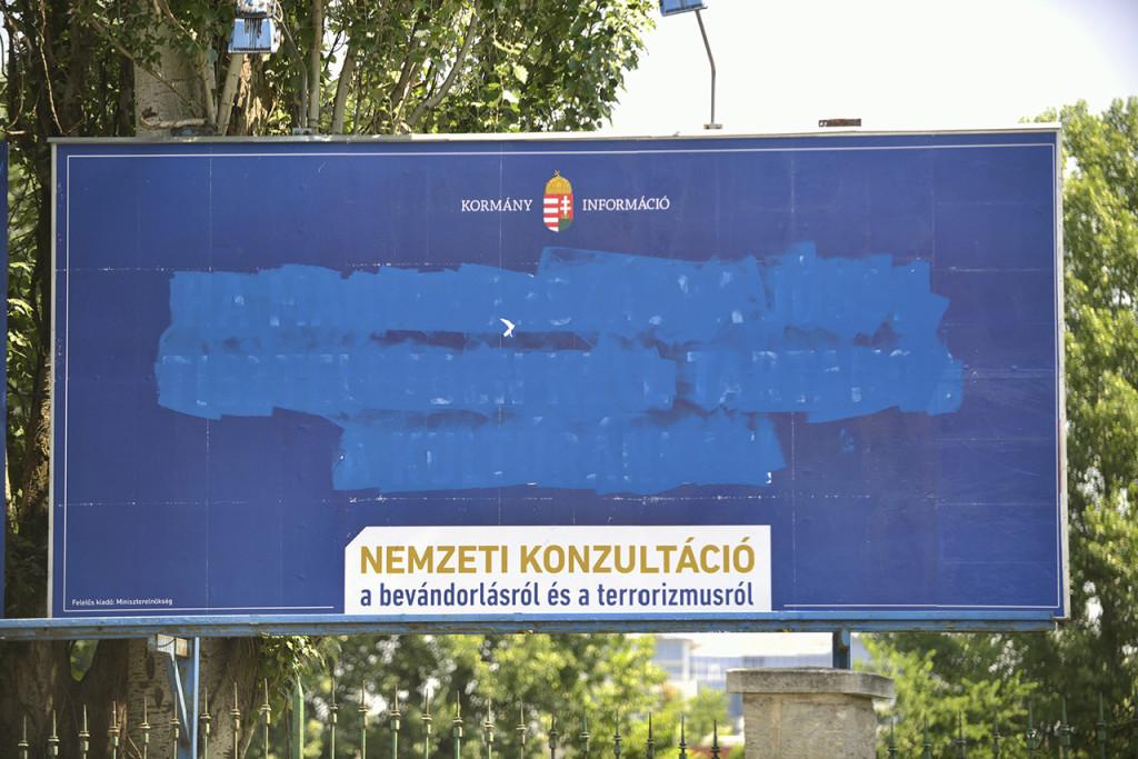 """Budapest, 2015. június 7. A kormány bevándorlásról szóló, megrongált plakátja a főváros XIII. kerületében, a Népfürdő utcában 2015. június 7-én. Több helyen megrongálták a plakátokat, ezért a Fidesz feljelentést tesz bűncselekményre felbujtás miatt. Németh Szilárd, az országgyűlési képviselője felszólította Szigetvári Viktort, az Együtt elnökét és párttársait, hogy """"ne uszítsák tovább az embereiket ilyen agresszív és törvénytelen cselekedetek elvégzésére"""". MTI Fotó: Marjai János"""