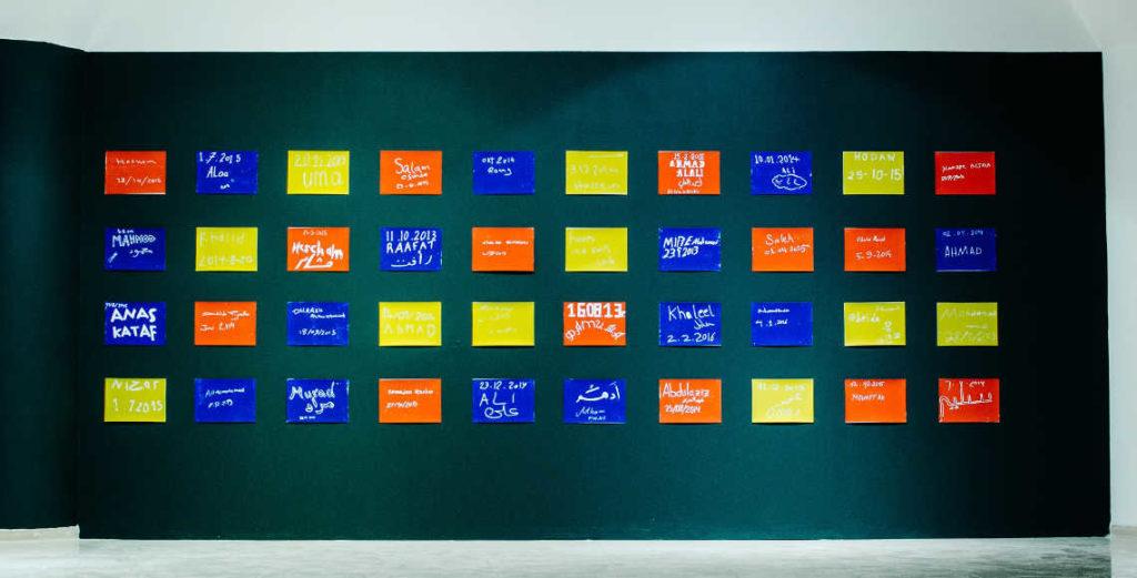 Тетради с зарисовками с судебных заседаний, планшетки с автографами и датами прибытия беженцев в Берлин, представленные на выставке, — это попытка персонализировать опыт такой обезличенной в риторике медиа и государства категории, как беженцы, сделать его материально и визуально ощутимым. Фото: Саша Коваленко